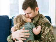 soldier in uniform hugging daughter