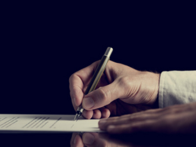 Retro image of a man signing a contract over dark background.