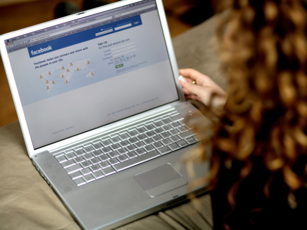Young female using Facebook on laptop