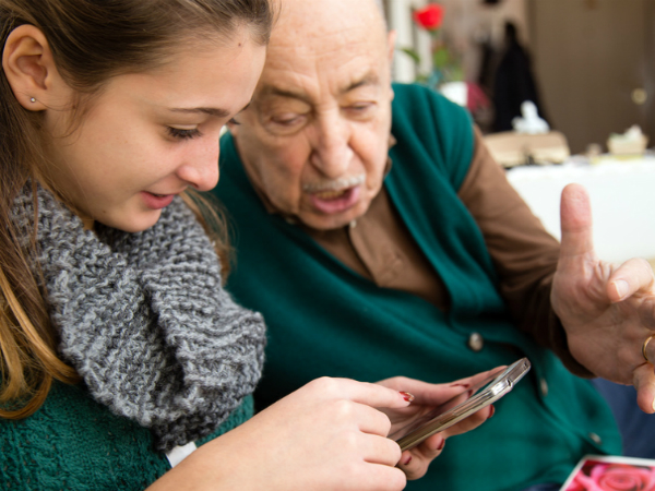 An older man and younger woman looking at a smartphone