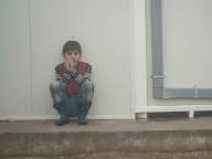 Boy sitting alone on pavement