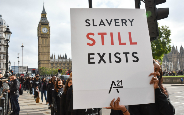 Description_of_photo_used_in_modern_slavery_article_protestor_holding_up_sign