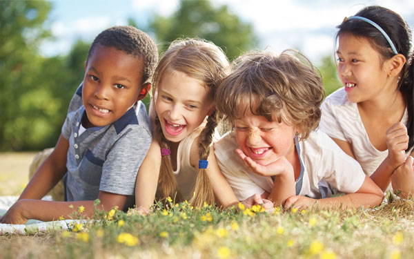 Description of image used in Caritas sponsored feature happy children lying on grass