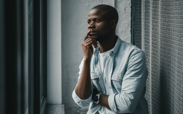 Portrait of young african american man looking at window