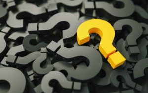Yellow question mark amid pile of black ones