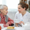 Care worker supporting an older person to eat
