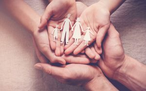 Image of joined hands holding a paper cutout of a family(Credit: sewcream / Adobe Stock)