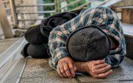 Homeless man sleeping on a step