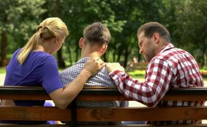 A boy being comforted by parents/carers