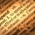Close-up of dictionary page showing definition of the word 'overspend' (credit: danheighton / Adobe Stock)