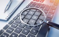 Image of magnifying glass, notebook and keyboard (credit: peterschreiber.media / Adobe Stock)