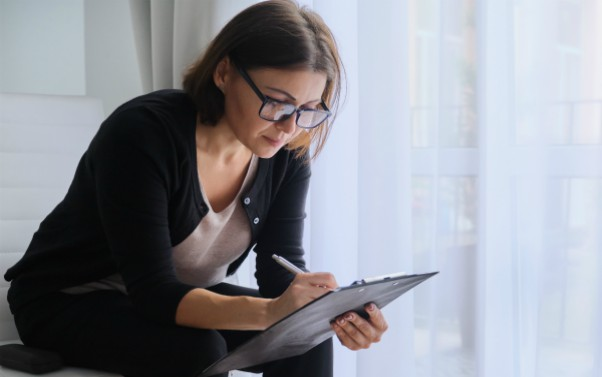 Female social worker writing notes on clipboard