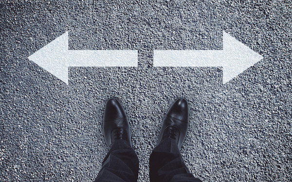Image of pair of feet and arrows signifying a crossroads or change of direction (credit: peshkov / Adobe Stock)