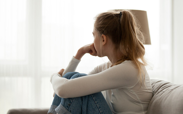 Image of teenager looking sadly towards window (credit: fizkes / Adobe Stock)