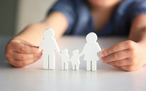Image of child holding cutouts of a family (credit: Africa Studio / Adobe Stock)