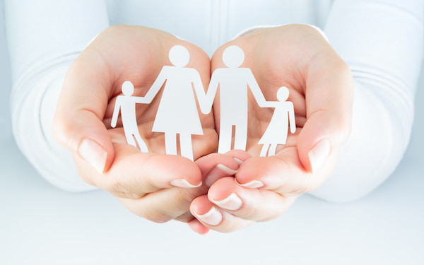 Image of cutouts representing family being held in hands (credit: Romolo Tavani / Adobe Stock)