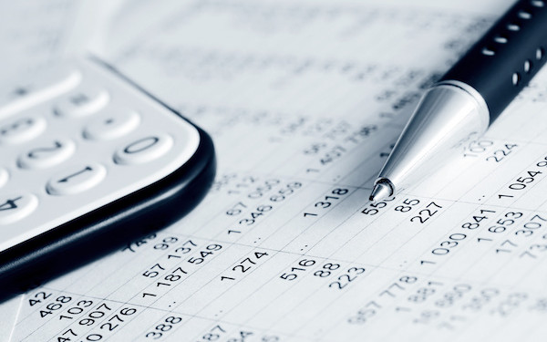 Image of accounts sheet with pen and calculator (credit: Wrangler / Adobe Stock)