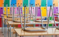 Image of empty classroom with chairs on desks (credit: miriristic / Adobe Stock)