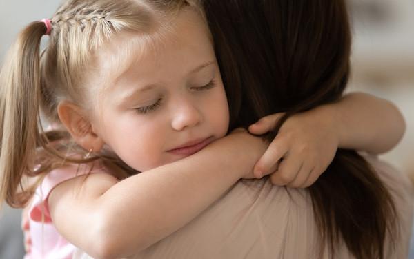 Image d'une fille embrassant sa mère adoptive (crédit : fizkes / Adobe Stock)