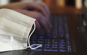Image of PPE mask resting on laptop (credit: raquel / Adobe Stock)