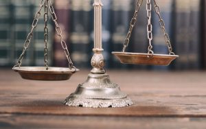 Image of scales of justice and law books (credit: Corgarashu / Adobe Stock)