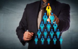 Image of person highlighted at top of employee hierarchy (credit: leowolfert / Adobe Stock)