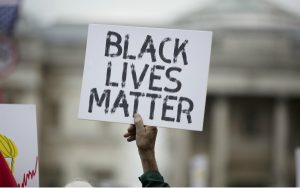 A person holding a Black Lives Matter poster at a protest