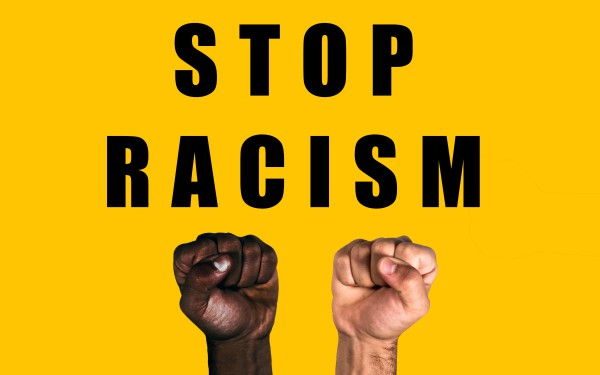 African black fist and caucasian white fist raised calling for freedom and equality on a yellow background. Multicultural fists raised. Stop racism.