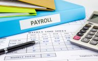 Image of payroll file and calculator (credit: vinnstock / Adobe Stock)