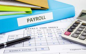 Image of payroll file and calculator (credit: vinnstock / Adobe Stock)