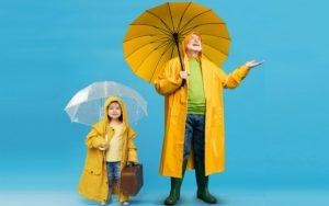 Man and girls holding up umbrellas