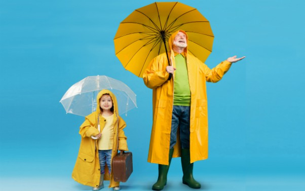 Man and girls holding up umbrellas