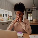 Image of young woman home working and looking tired and stressed (credit: StratfordProductions / Adobe Stock)