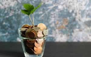 Glass of money and plant growing from it