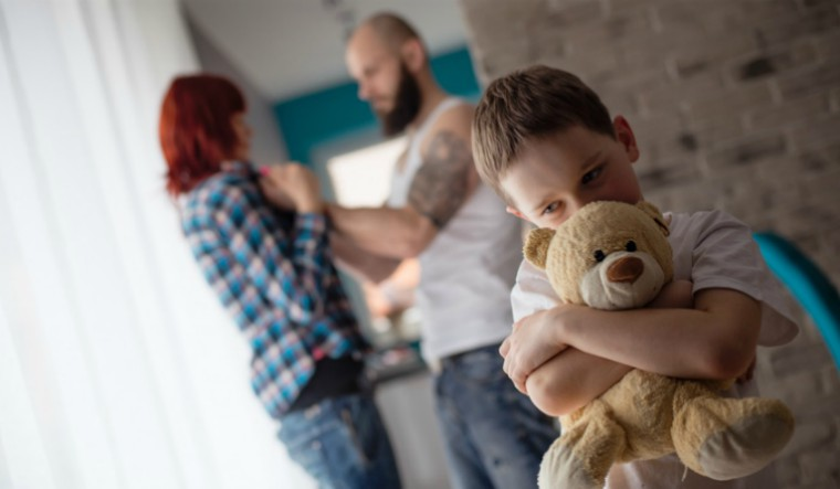 A child hugs a teddy bear in the foreground while in the background a person with a beard is holding someone with red hair threateningly