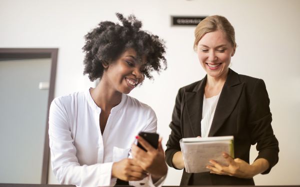 A white and a Black woman talking in the workplace