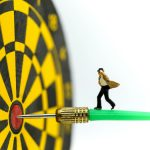 Miniature people: businessman on dart arrow hitting in the target center of dartboard,Target business, achieve and victory concept .